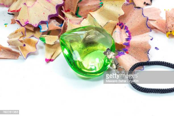 Close-Up Of Pencil Shavings And Heart Shape Locket Over White Background