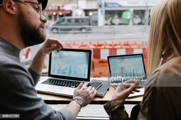 Close-up of people working in Cafe on Laptops