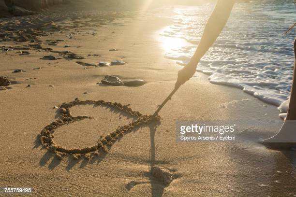 Close-Up Of Person Drawing Heart On Sand At Beach