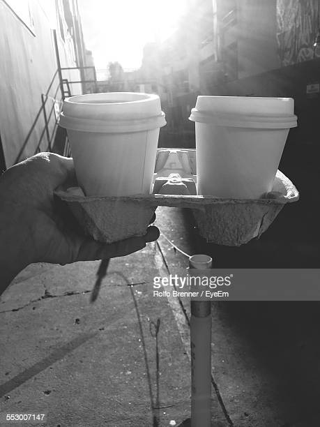 Close-Up Of Person Hand Holding Disposable Coffee Cups