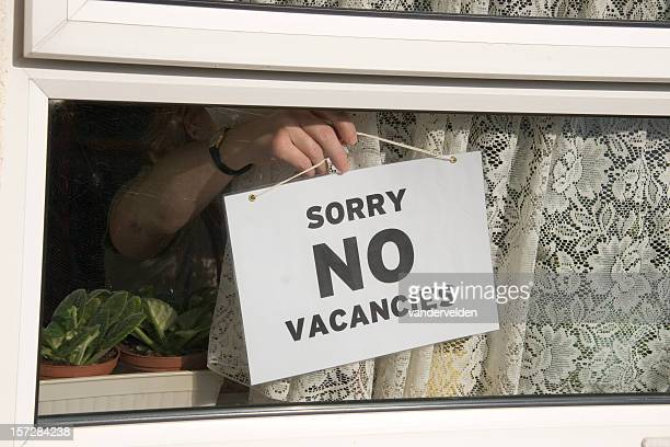 Close-up of person hanging No Vacancies sign on window