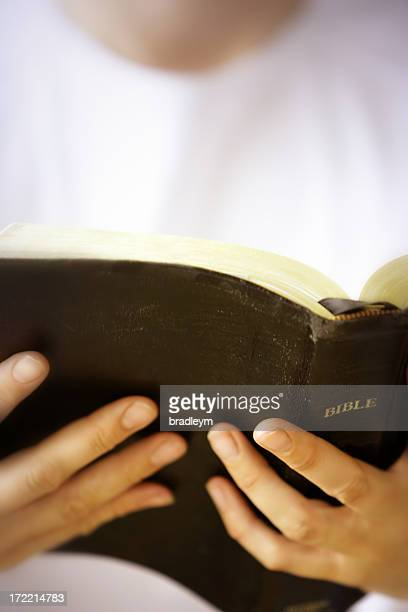 Close-up of person in white shirt reading Bible