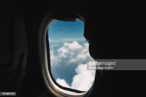 Close-Up Of Person Looking At Clouds Through Airplane Window