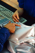 Close-up of person pointing out stain on silk blouse