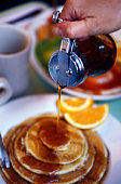 Close-up of person pouring syrup on pancakes