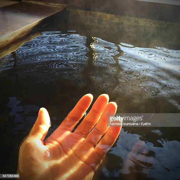 Close-Up Of Person Wet Hand Over Hot Spring