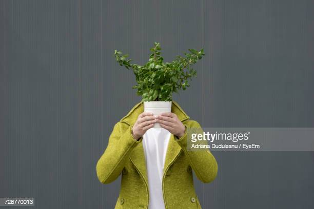 Close-Up Of Person With Potted Plant Against Grey Background