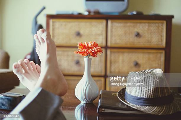 Close-Up Of Persons Feet Resting On Coffee Table Near Vase And Hat