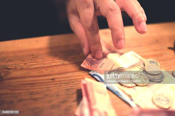Close-Up Of Persons Hand Paying Money
