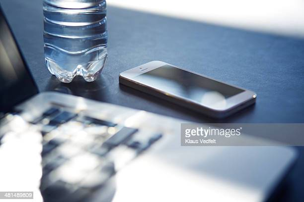 Close-up of phone, laptop & waterbottle
