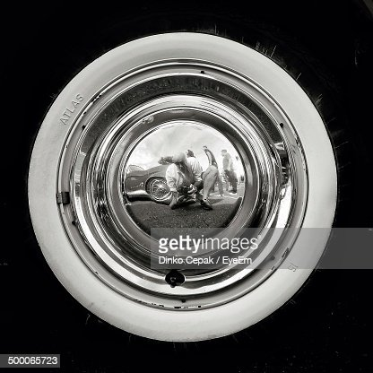 Close-up of photographer catches reflection of himself in hubcap