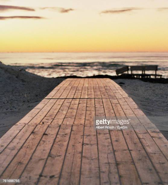 Close-Up Of Pier At Beach During Sunset