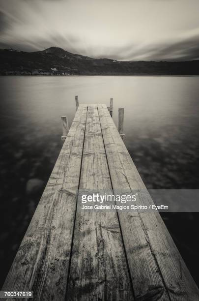 Close-Up Of Pier Over Lake Against Sky