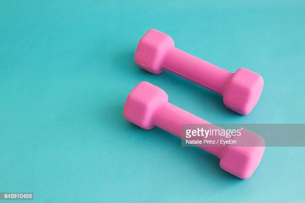 Close-Up Of Pink Dumbbells On Turquoise Background