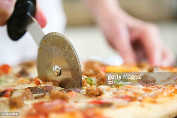 Closeup of Pizza Being Cut by Cutter