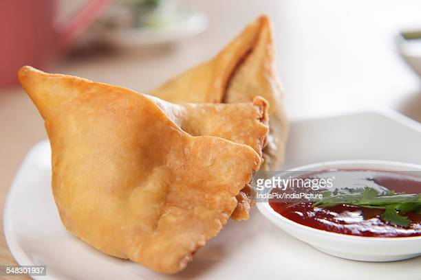 Close-up of plate of samosa with tomato sauce