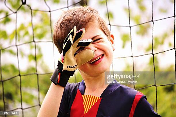 Close-Up Of Playful Boy Making Face Against Netting On Soccer Field