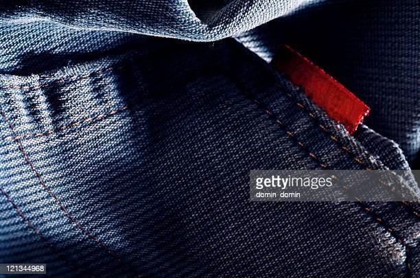 Close-up de bolso jeans azul e rótulo vermelho, studio