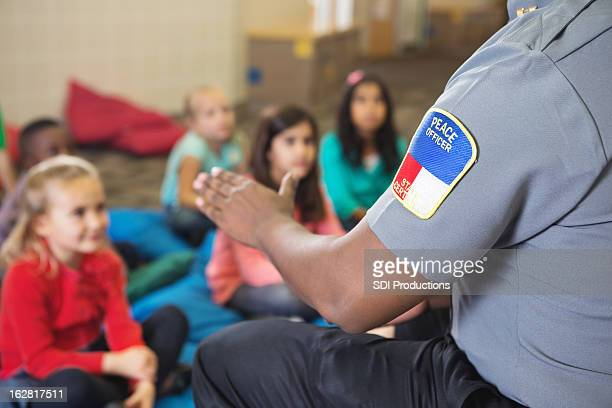 Closeup of police officer talking to young class on campus