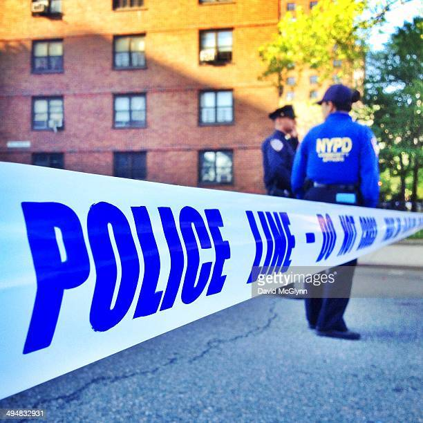 Closeup of police tape with NYPD officers in background at scene of shooting on E 102nd St New York City