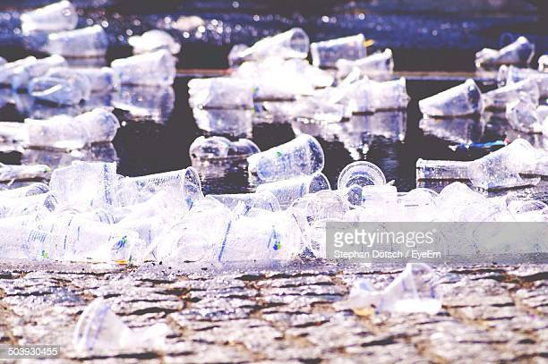 Close-up of polluted beach with plastic glasses floating on water