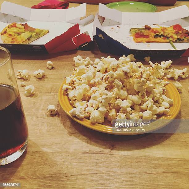 Close-Up Of Popcorn And Pizza With Drink On Table