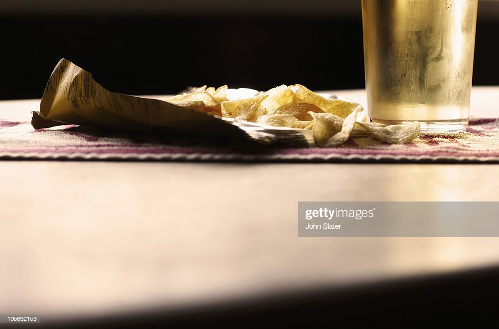 close-up of potato chips and cider on bar