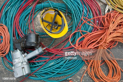 Close-up of power cords and air hoses with a nail gun and a hardhat at a construction site : Stock Photo