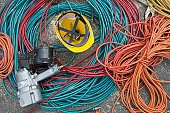 Close-up of power cords and air hoses with a nail gun and a hardhat at a construction site