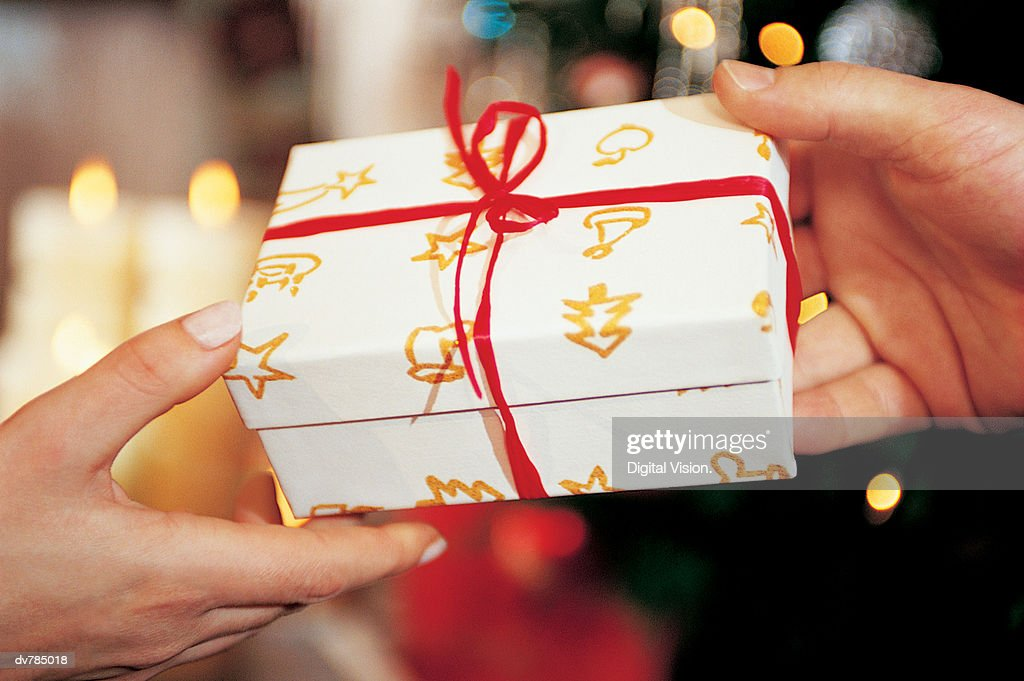 Close-Up of Present Being Handed Over at Christmas : Stock Photo
