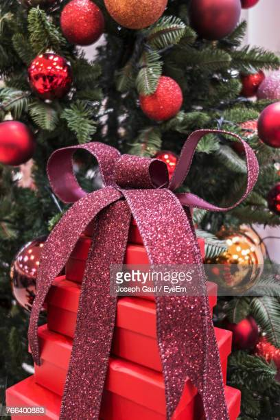 Close-Up Of Presents Against Christmas Tree