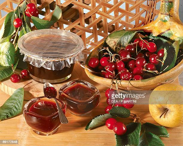 Closeup of preserved cherries with fresh cherries and a green apple