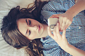 Closeup of sad teenage girl lying in bed using her mobile. Young pretty woman with bored expression looking at message on her cell phone, reading or waiting for call.