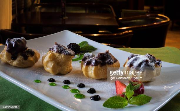 Close-Up Of Profiteroles Garnished With Fruits In Tray On Table
