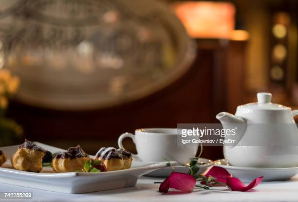 Close-Up Of Profiteroles In Tray By Cup And Teapot On Table