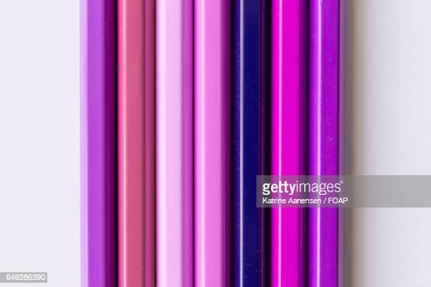 Close-up of purple pencils against white background
