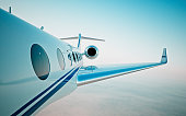 Closeup of realistic photo white, luxury generic design private jet flying over the clouds.Modern airplane and empty blue sky on background. Business travel concept. Horizontal. 3d rendering