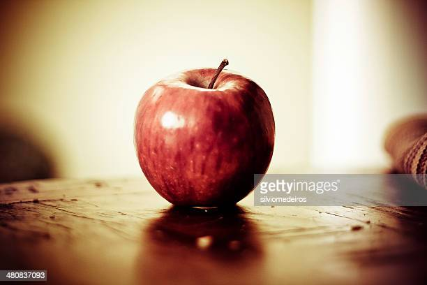 Close-up of red apple on wooden table