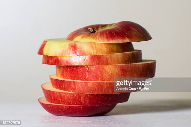Close-Up Of Red Apple Slices Against White Background