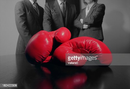 Close-up of Red Boxing Gloves with Business Persons