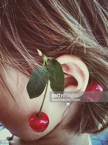 Close-Up Of Red Cherries On Girl Ear