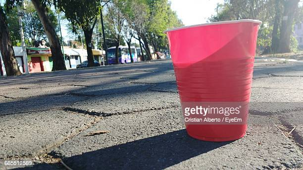 Close-Up Of Red Disposable Cup On Footpath