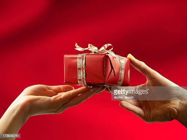 Nahaufnahme von roten Geschenk, das von Mann und Frau