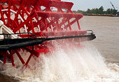 Close-up of red paddle boat wheel splashing in the water