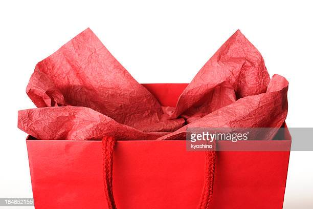 Close-up of red shopping bag with decoration against white background