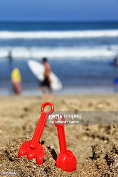 Close-Up Of Red Shovel In Sand