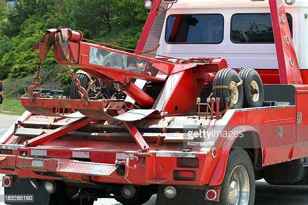 Close-up of red tow truck in a road near trees