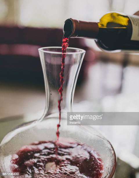 Close-up of red wine being poured in a wine decanter, part of the oxygenating process.