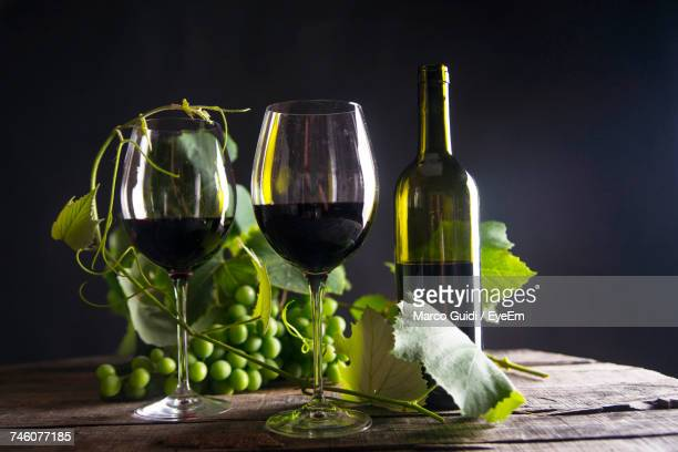 Close-Up Of Red Wine With Grapes On Table