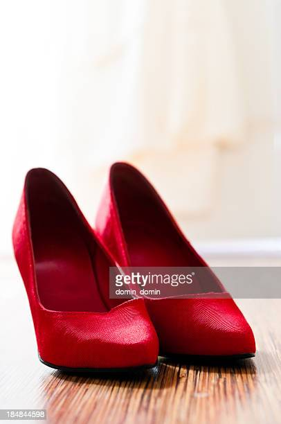 Close-up of red woman's high-heel shoes standing on the floor